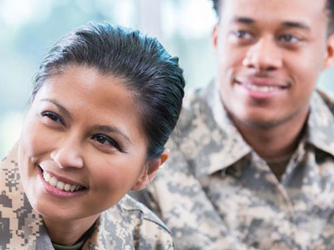 Two individuals in military attire smile while learning about financial aid options and prior learning credit.